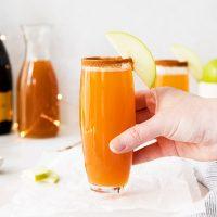 hand on glass of apple cider mimosas
